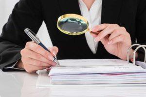 Persona de Inspección de Trabaj analiza la documentación de una evaluación psicosocial.